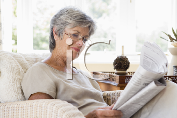 Royalty Free Photo of a Woman Reading a Newspaper