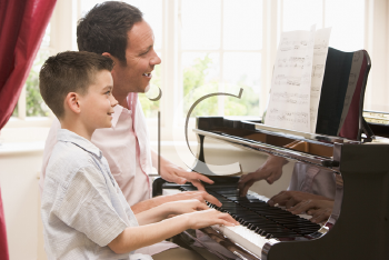 Royalty Free Photo of a Man Teaching a Boy Piano