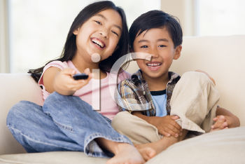 Royalty Free Photo of Siblings Watching Television