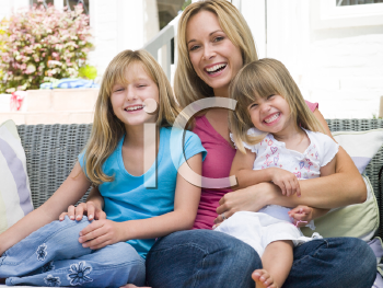 Royalty Free Photo of a Mother and Two Girls Sitting Outside