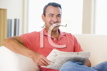Royalty Free Photo of a Man Reading a Newspaper on the Couch