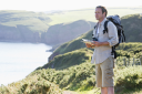 Royalty Free Photo of a Man on a Cliff With a Map