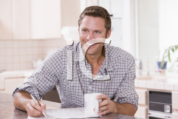 Royalty Free Photo of a Man Reading a Newspaper and Holding a Coffee