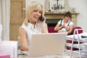 Royalty Free Photo of a Woman in a Home Office With a Woman Feeding a Baby in the Background