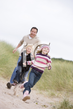 Royalty Free Photo of a Father and Two Children Running at the Beach