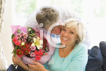 Royalty Free Photo of a Man Giving His Wife Flowers and Kissing Her Cheek