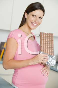 Royalty Free Photo of a Pregnant Woman With a Chocolate Bar