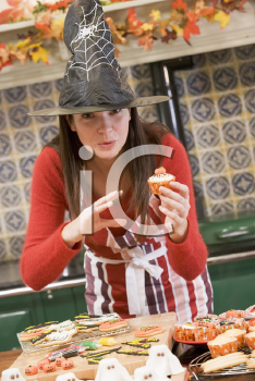 Royalty Free Photo of a Woman in a Witch Hat Making Halloween Treats