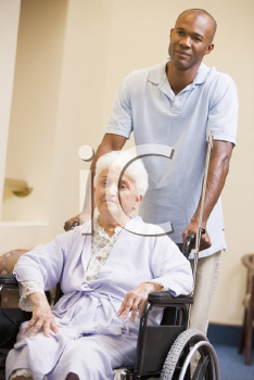 Royalty Free Photo of a Mam Pushing a Woman in a Wheelchair