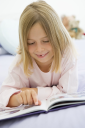 Royalty Free Photo of a Girl Lying on Her Bed Reading a Book