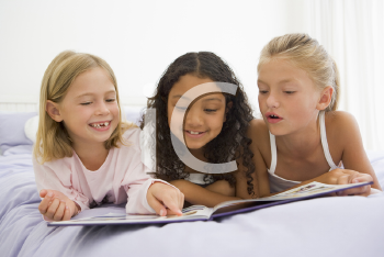 Royalty Free Photo of Three Girls Lying on a Bed Reading a Story