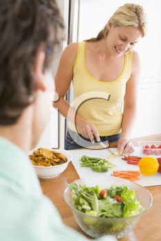 Royalty Free Photo of a Woman Talking to Her Husband While Preparing a Meal