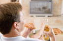 Royalty Free Photo of a Man Drinking Beer and Eating Pizza in Front of the TV