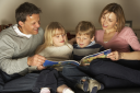 Royalty Free Photo of a Family Reading a Book
