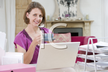 Royalty Free Photo of a Woman Drinking Coffee at Her Desk