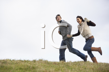 Royalty Free Photo of a Couple Running in a Park