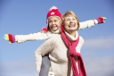 Royalty Free Photo of a Grandmother Giving Her Granddaughter a Piggyback Ride