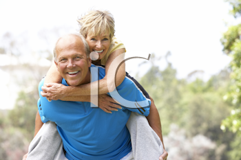 Royalty Free Photo of a Man Giving a Woman a Piggyback Ride