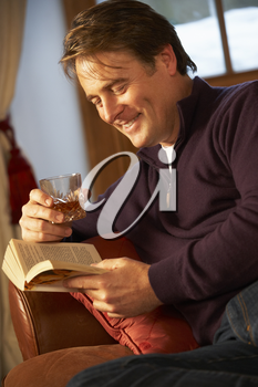 Middle Aged Man Relaxing With Book Sitting On Sofa Drinking Whisky