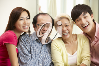 Portrait Of Chinese Parents With Adult Children Relaxing At Home Together