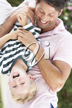 Father Holding Son Upside Down Outdoors