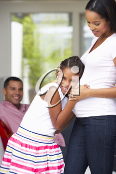 Daughter Listening To Pregnant Mother's Stomach