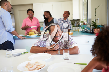 Multi-Generation Family Preparing For Meal At Home