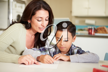 Hispanic Mother Helping Son With Homework At Table