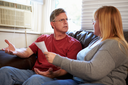 Worried Couple Sitting On Sofa Arguing About Bills