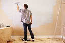 Man Decorating Room Using Paint Roller On Wall