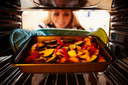 Woman Putting Dish Of Vegetables Into Oven To Roast