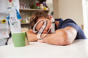 Tired Man Asleep At Kitchen Table Next To Mobile Phone