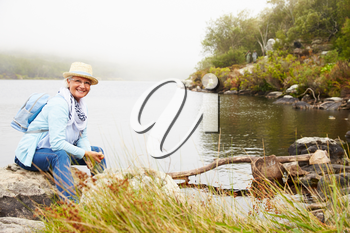 Senior woman with a hat sitting by a lake, smiling to camera