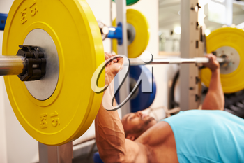 Young man bench pressing weights at a gym, side view