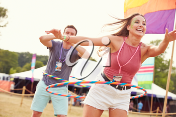 Woman with hula hoop at a music festival, man in background
