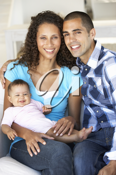Young Family With Baby Relaxing On Sofa At Home
