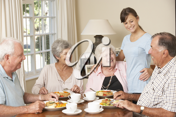 Group Of Senior Couples Enjoying Meal Together In Care Home With Teenage Helper