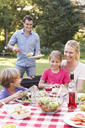 Family Enjoying Barbeque In Garden Together