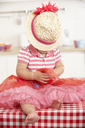 Little Girl Sitting On Kitchen Table Wearing Hat