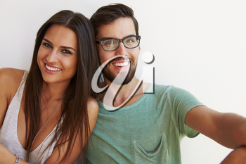 Portrait Of Couple Sitting Against White Wall