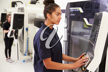 Female Engineer Operating CNC Machinery On Factory Floor