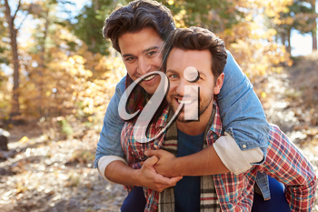 Portrait Of Gay Male Couple Walking Through Fall Woodland