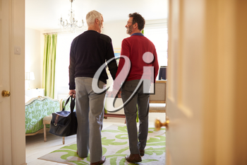 Middle aged male couple walk in to a hotel room, back view