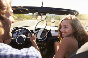 Couple in open top car look at each other, passenger POV