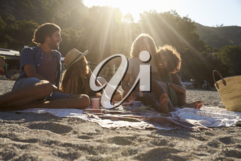 Two couples having a picnic on the beach, lens flare, Ibiza
