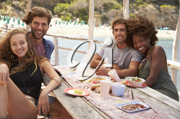 Four friends sitting at a table by the sea look to camera