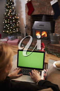 Woman Using Laptop In Room Decorated For Christmas