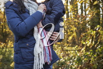 Mother Cuddling Daughter On Walk In Autumn Countryside