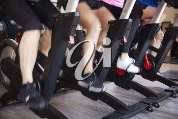 Close Up Of Feet On Exercise Bikes In Gym Spinning Class