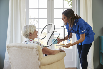 Nurse serving tea and biscuits to senior woman at home